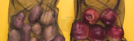 top view of potatoes and apples in eco friendly black mesh bags isolated on yellow, panoramic shot