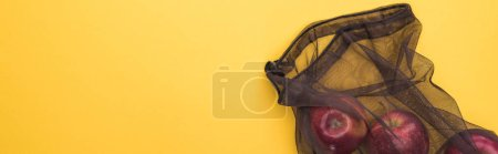 top view of apples in eco friendly black mesh bag isolated on yellow, panoramic shot