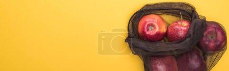 Foto de Vista superior de las manzanas en bolsa de malla negra ecológica aislada en amarillo, tiro panorámico - Imagen libre de derechos