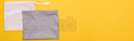 Foto de Vista superior de algodón blanco y gris bolsas ecológicas aisladas en amarillo, tiro panorámico - Imagen libre de derechos