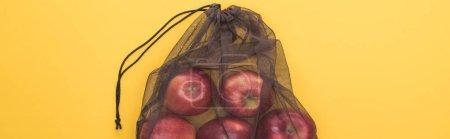 Foto de Vista superior de las manzanas rojas en bolsa de malla negra ecológica aislada en amarillo, tiro panorámico - Imagen libre de derechos
