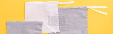 Photo for Top view of cotton eco friendly bags isolated on yellow, panoramic shot - Royalty Free Image
