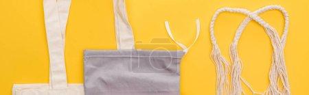 Photo pour Vue du haut des sacs écologiques de coton d'isolement sur le projectile jaune et panoramique - image libre de droit