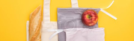 Photo for Top view of ripe apple, baguette on eco friendly bags isolated on yellow, panoramic shot - Royalty Free Image