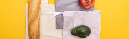 Photo for Top view of apple, baguette and avocado on eco friendly bags isolated on yellow, panoramic shot - Royalty Free Image