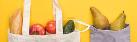 Photo for Top view of ripe fruits, vegetables and baguette in eco friendly bags isolated on yellow, panoramic shot - Royalty Free Image
