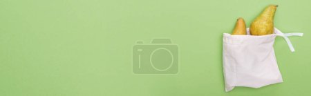 Photo for Top view of pears in eco friendly white bag isolated on green, panoramic shot - Royalty Free Image