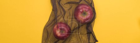 Photo for Top view of red apples in eco friendly black bag isolated on yellow, panoramic shot - Royalty Free Image