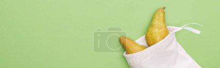 Photo pour Vue du haut des poires dans le sac blanc écologique-amical d'isolement sur le vert, projectile panoramique - image libre de droit