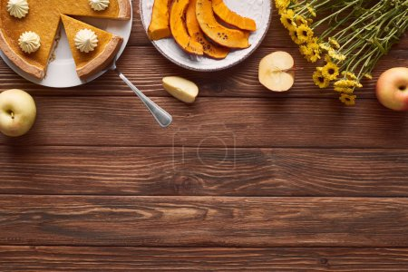 Photo for Delicious, cut pumpkin pie with whipped cream near sliced baked pumpkin, yellow flowers, cut and whole apples on brown wooden table - Royalty Free Image