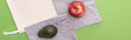 Photo for Top view of apple and avocado on eco friendly bags isolated on green, panoramic shot - Royalty Free Image