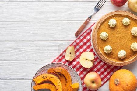 tarte à la citrouille savoureuse avec crème fouettée sur une serviette à carreaux près de citrouilles crues et tranchées cuites au four, pommes coupées et entières, et fourchette sur une table en bois blanc