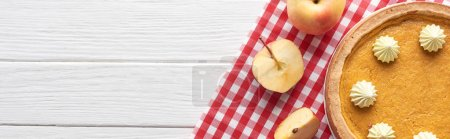 Photo for Tasty pumpkin pie with whipped cream on checkered napkin near cut and whole apples on white wooden table - Royalty Free Image