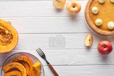 Photo pour Tarte à la citrouille savoureuse avec crème fouettée près de la citrouille crue et tranchée cuite au four, pommes coupées et entières, et fourchette sur table en bois blanc - image libre de droit