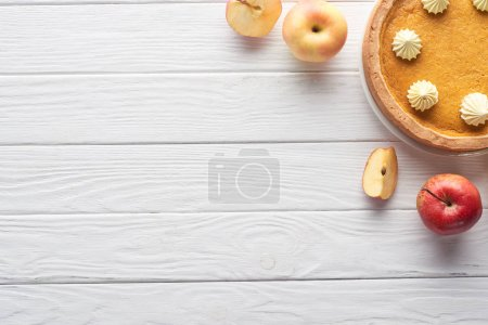 Photo for Top view of delicious pumpkin pie with whipped cream near cut and whole apples on white wooden table - Royalty Free Image