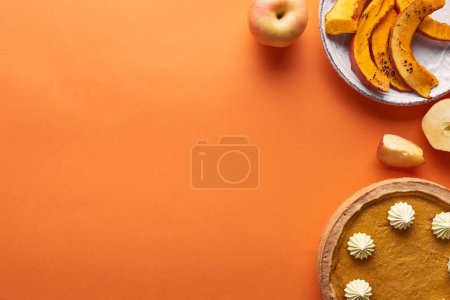 Photo for Delicious pumpkin pie with whipped cream near sliced baked pumpkin, whole and cut apples on orange surface - Royalty Free Image