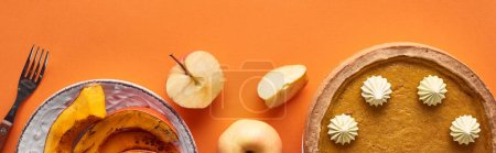 Photo pour Plan panoramique de délicieuse tarte à la citrouille avec crème fouettée près de tranches de citrouille cuite au four, pommes entières et coupées, et fourchette sur la surface orange - image libre de droit