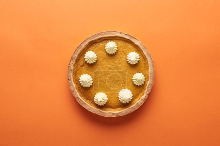 Photo for Top view of delicious pumpkin pie with whipped cream on orange surface - Royalty Free Image