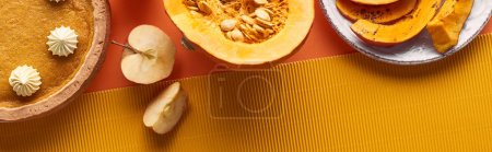 Photo for Panoramic shot of pumpkin pie with whipped cream near raw and baked pumpkins, cut apples, and textured napkin on orange surface - Royalty Free Image