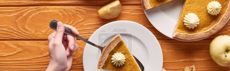 Photo for Cropped view of woman holding spatula with piece of pumpkin pie with whipped cream near cut and whole apples on orange wooden table, panoramic shot - Royalty Free Image