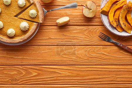 Photo for Delicious pumpkin pie with whipped cream near sliced baked pumpkin, cut apple, and fork on orange wooden table - Royalty Free Image