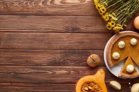 Photo for Tasty pumpkin pie with whipped cream near whole and cut apples, half of raw pumpkin, and yellow flowers on brown wooden surface - Royalty Free Image