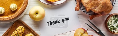 Photo for Top view of roasted turkey, pumpkin pie and grilled vegetables served near thank you card on white wooden table - Royalty Free Image