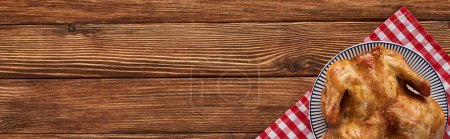top view of roasted turkey on red plaid napkin served on wooden table, panoramic shot