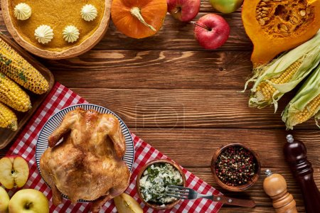 Photo for Top view of roasted turkey, pumpkin pie and grilled vegetables served on wooden table - Royalty Free Image