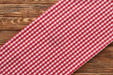 Photo for Top view of red plaid napkin on wooden table - Royalty Free Image