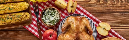 top view of roasted turkey, grilled corn and apples served on wooden table with red napkin, panoramic shot