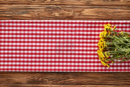 Photo for Top view of yellow wildflowers on plaid red napkin on wooden table - Royalty Free Image