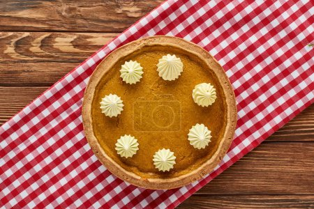 Photo for Top view of delicious pumpkin pie served on rustic plaid napkin on wooden table - Royalty Free Image