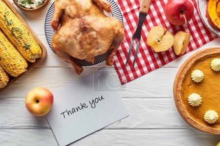 Photo pour Vue du dessus de dinde rôtie, tarte à la citrouille et légumes grillés servis sur une table en bois blanc avec serviette à carreaux rouge et carte de remerciement - image libre de droit