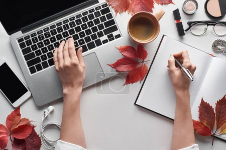 Photo for Cropped view of woman using laptop and holding pen near notebook, cosmetics, glasses, earphones, smartphone and red leaves of wild grapes on white table - Royalty Free Image