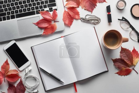 Photo pour Top view of laptop near smartphone, coffee cup, cosmetics, earphones, glasses, notebook and red leaves of wild grapes on white table. - image libre de droit