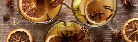 Photo for Top view of traditional pear mulled wine in glasses with spices on wooden rustic table, panoramic shot - Royalty Free Image