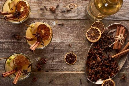 Photo pour Vue de dessus du vin chaud traditionnel poire avec des épices sur table rustique en bois - image libre de droit