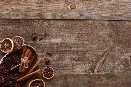 Photo pour Vue du dessus de bâtonnets de cannelle, d'anis et d'agrumes séchés sur table rustique en bois - image libre de droit