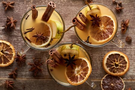 Photo for Top view of seasonal pear mulled wine cocktails with spices and dried citrus on wooden rustic table - Royalty Free Image
