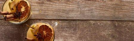 Photo pour Vue du dessus du vin chaud poire chaud avec des épices et agrumes séchés sur table en bois, panoramique - image libre de droit