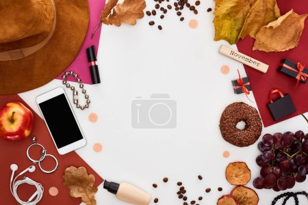 Photo for Smartphone, hat, dry leaves, fresh and dry apples, grapes, donut, cosmetics, coffee grains and wooden block with november inscription isolated on white - Royalty Free Image