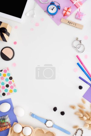 Foto de Digital tablet, easter pastry decoration, chicken eggs, cosmetics, blackberry, gift boxes, felt pens, spikelets, wristwatch, wooden block with april inscription isolated on white - Imagen libre de derechos