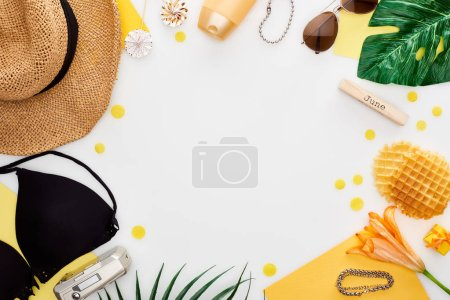 Photo for Wooden block with june inscription, straw hat, digital camera, lily flower, green leaves, sunglasses, sunscreen, lollipops, waffles, bikini bra isolated on white - Royalty Free Image