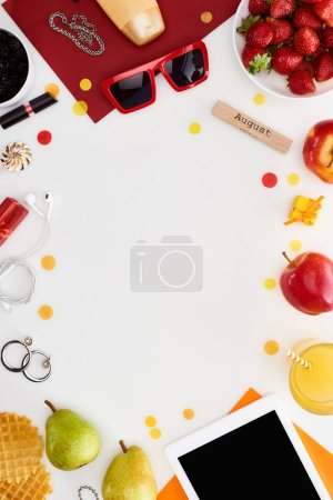 Photo for Wooden block with august inscription, digital tablet, sunglasses, orange juice, fruits, waffles, cosmetics, earphones isolated on white - Royalty Free Image