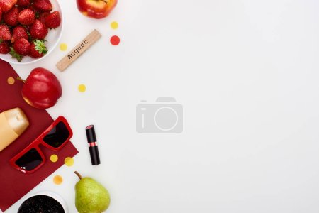 Photo for Fresh strawberry, apples, pear, sunglasses, cosmetics, red paper, wooden block with august inscription isolated on white - Royalty Free Image