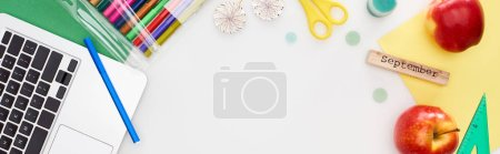 Photo for Panoramic shot of laptop, felt pens, apple, lollipops, scissors, wooden block with september inscription, multicolored paper isolated on white - Royalty Free Image
