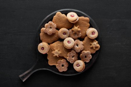 Photo for Top view of Christmas cookies in pan on black wooden table - Royalty Free Image