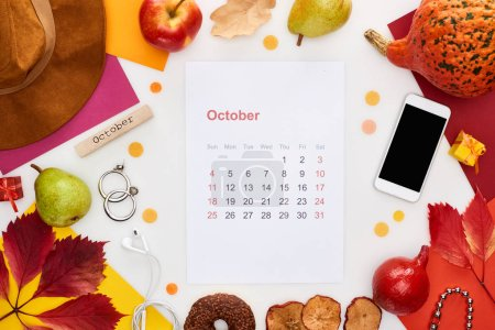Photo for October calendar page, hat, smartphone, fruits, pumpkin, dry leaves, multicolored papers,  wooden block with november inscription isolated on white - Royalty Free Image