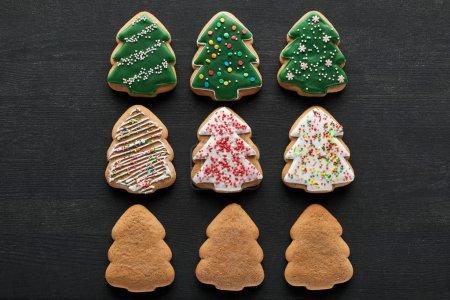 Photo pour Plat sur fond noir avec de délicieux biscuits glacés aux arbres de Noël - image libre de droit